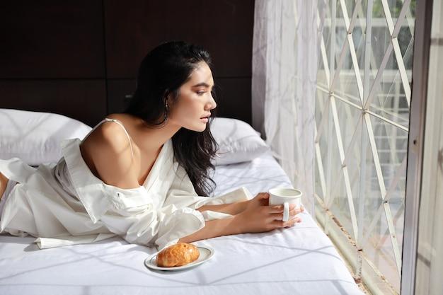 Joven atractiva comiendo café y croissant para el desayuno en la cama en su casa por la mañana