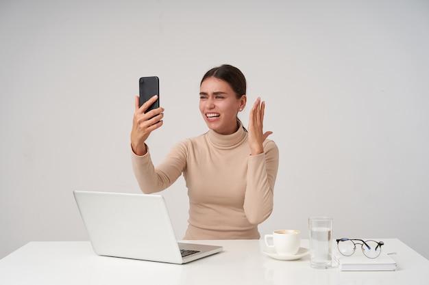 Joven y atractiva dama de cabello oscuro levantando la mano con el teléfono inteligente mientras tiene una conversación telefónica emocionante, trabajando en la oficina con un portátil moderno