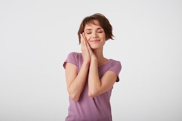 Joven y atractiva dama de pelo corto en camiseta en blanco, finge dormir, se apoya en las manos, tiene una sonrisa tierna, toma la siesta. de pie sobre fondo blanco.