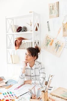 Joven y atractiva diseñadora femenina creando ropa nueva