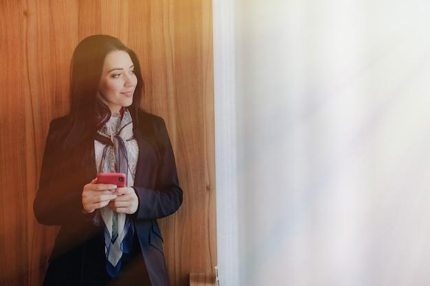 Joven atractiva emocional en ropa de estilo de negocios en una ventana