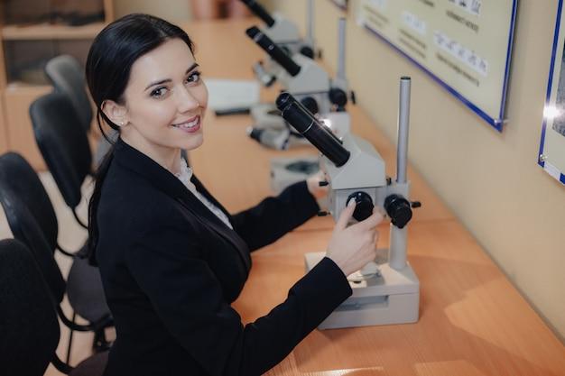 Joven atractiva emocional sentado en la mesa y trabajando con un microscopio en una oficina moderna o audiencia