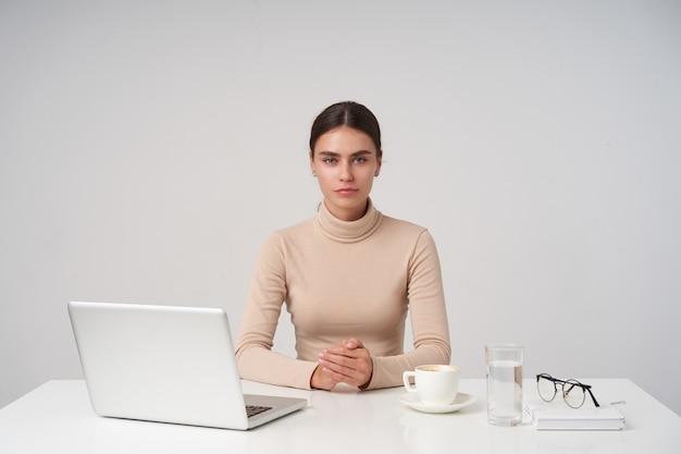Joven y atractiva empresaria de pelo oscuro sentado a la mesa y cruzando las manos sobre la encimera, aislado sobre una pared blanca en ropa formal