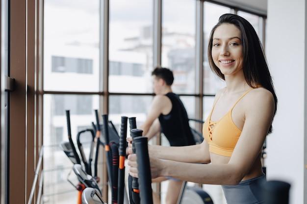 Joven atractiva en el gimnasio en bicicleta estática, fitness y yoga