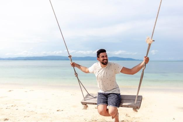 Joven atractiva mezcla feliz corrió hombre balanceándose en un columpio en la orilla de un mar tropical brillante
