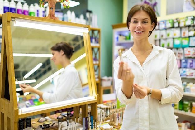 Joven y atractiva morena se ve de pie frente al espejo con el lápiz en sus manos