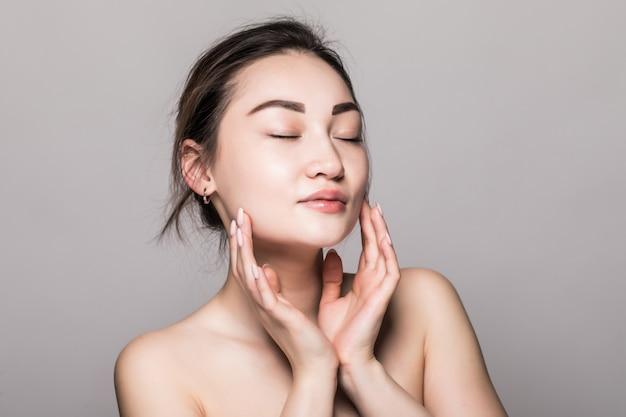 Joven y atractiva mujer asiática cuidado de la piel en la pared gris