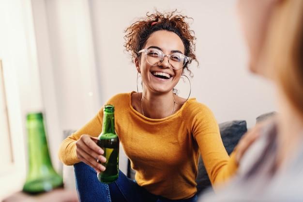 Joven y atractiva mujer caucásica bronceada sonriente con el pelo rizado sentado con su mejor amiga, charlando y bebiendo cerveza.