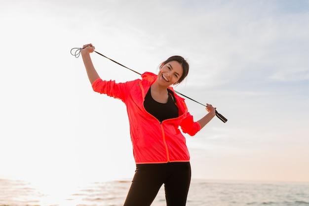 Joven y atractiva mujer delgada haciendo ejercicios deportivos en el amanecer de la mañana en la playa del mar en ropa deportiva, estilo de vida saludable, con chaqueta cortavientos rosa, sosteniendo la cuerda para saltar