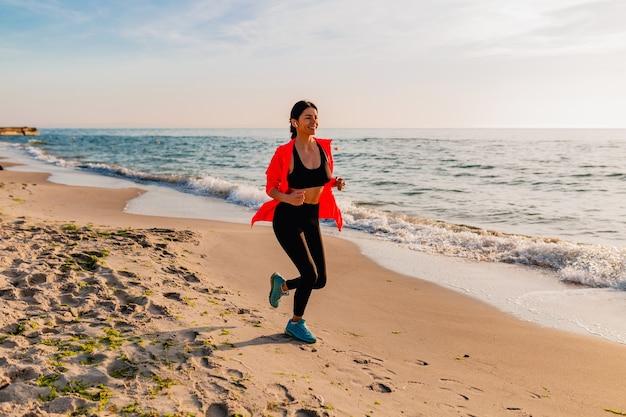 Joven y atractiva mujer delgada haciendo ejercicios deportivos en el amanecer de la mañana trotando en la playa del mar en ropa deportiva, estilo de vida saludable, escuchando música en auriculares, con chaqueta cortavientos rosa