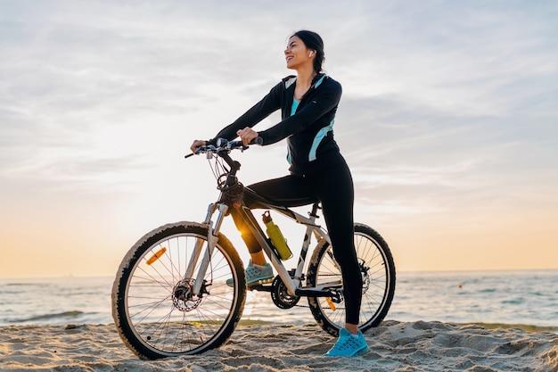 Joven y atractiva mujer delgada montando bicicleta, deporte en la playa de verano amanecer de mañana en ropa deportiva, estilo de vida activo y saludable, sonriendo feliz divirtiéndose
