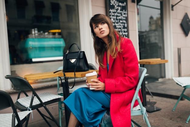 Joven y atractiva mujer elegante sentada en el café de la calle de la ciudad en abrigo rojo bebiendo café con vestido azul