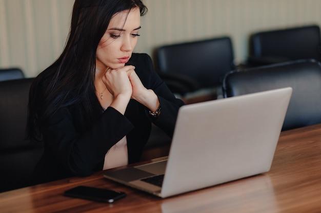 Joven atractiva mujer emocional en ropa de estilo empresarial sentado en el escritorio con una computadora portátil