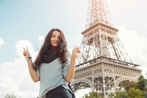 Joven atractiva mujer feliz mostrando gesto de paz torre eiffel en parís, francia