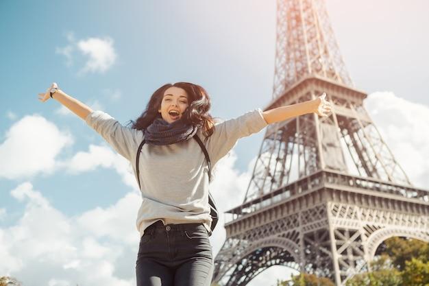 Joven atractiva mujer feliz saltando de alegría contra la torre eiffel en parís, francia