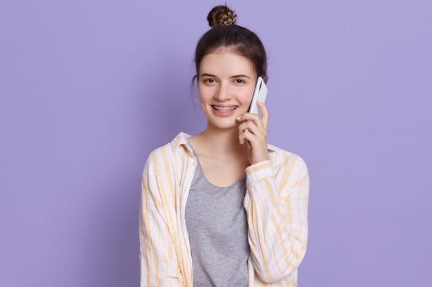 Joven y atractiva mujer joven de pelo oscuro con teléfono móvil conversando con un amigo