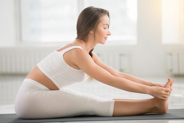 Joven atractiva mujer sentada en paschimottanasana pose, blanco