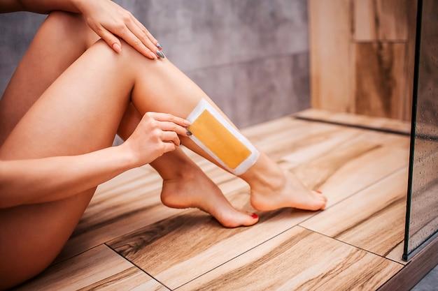 Joven atractiva mujer sexy en la ducha. corte la vista del cuerpo desnudo de la modelo sentado en el piso de madera y haciendo la depilación sola.