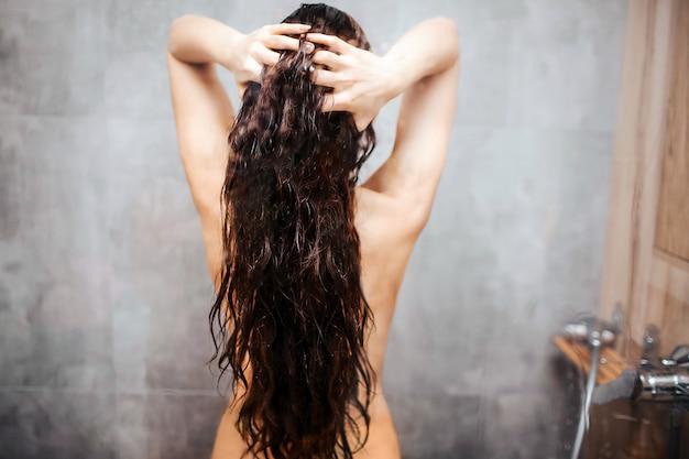 Joven atractiva mujer sexy en la ducha. modelo caucásico de cabello oscuro con cuerpo delgado y bien construido pararse y sostener el cabello entre las manos. hermosa forma