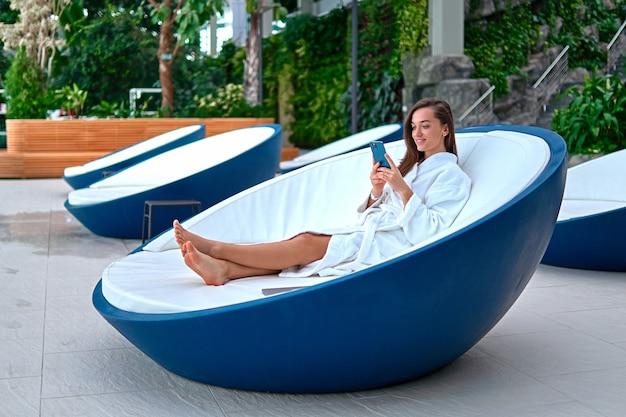 Joven y atractiva mujer sonriente con bata de baño blanca con teléfono inteligente para ver videos y navegar en línea mientras está acostado en una tumbona durante la relajación en el balneario