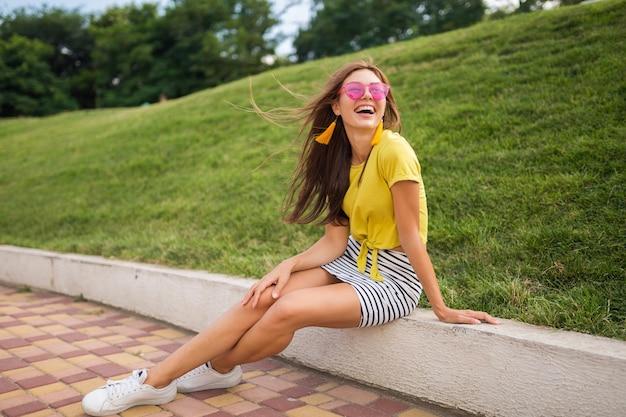 Joven y atractiva mujer sonriente con estilo divirtiéndose en el parque de la ciudad, positiva, emocional, con top amarillo, minifalda a rayas, gafas de sol rosas, zapatillas blancas, tendencia de moda de estilo veraniego, piernas largas