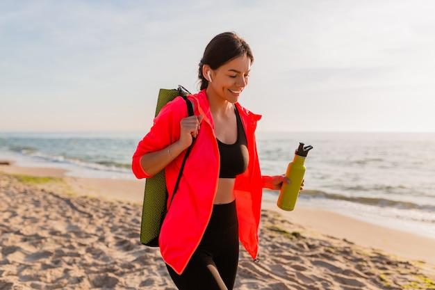 Joven y atractiva mujer sonriente haciendo deporte en el amanecer de la mañana en la playa del mar sosteniendo una estera de yoga y una botella de agua, estilo de vida saludable, escuchando música en auriculares, vistiendo una chaqueta cortavientos rosa