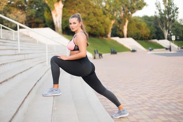 Joven atractiva mujer de talla grande en top deportivo y polainas pensativamente mientras se estira en las escaleras en el parque de la ciudad