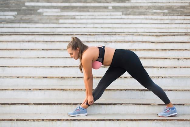 Joven y atractiva mujer de talla grande en top deportivo y polainas que se extienden en las escaleras mientras pasa tiempo al aire libre