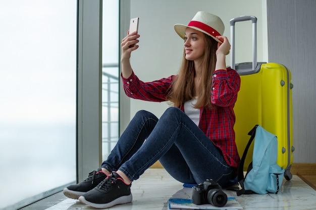 Joven y atractiva mujer viajera en ropa casual con una maleta amarilla