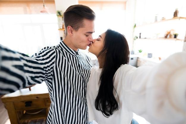 Joven atractiva pareja besándose y tomando selfie