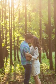 Joven atractiva pareja de enamorados besándose en la naturaleza de verano