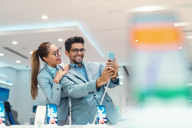 Joven atractiva pareja multicultural vestida elegante tomando selfie con nuevo teléfono inteligente en la tienda de tecnología.