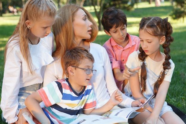 Joven y atractiva profesora leyendo un libro a sus pequeños alumnos