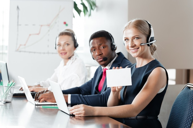 Joven atractiva trabajando en un call center con sus colegas