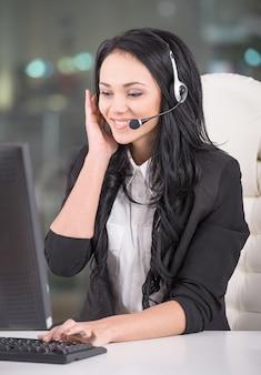 Joven atractiva está trabajando en un centro de llamadas.