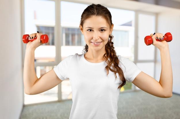 Joven atractiva trabajando con pesas