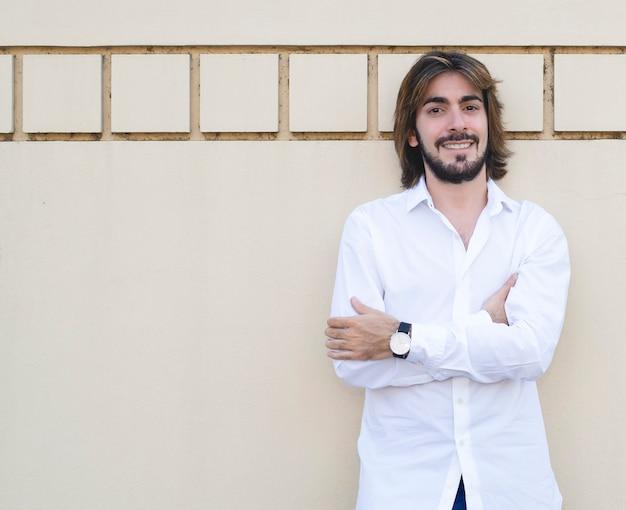 Joven atractivo con cabello largo y barba, vestido con camisa blanca se apoya en la pared amarilla y sonríe
