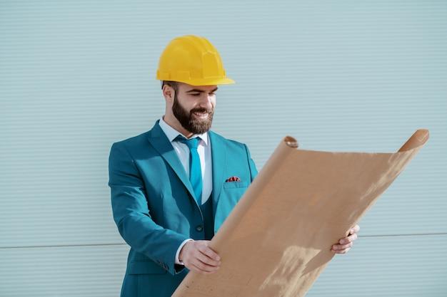 Joven atractivo exitoso arquitecto barbudo caucásico con casco amarillo en la cabeza y en traje azul mirando planos mientras está de pie en el sitio.