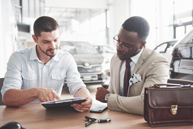 Un joven y atractivo hombre de negocios negro compra un auto nuevo, firma un contrato y le entrega las llaves al gerente.