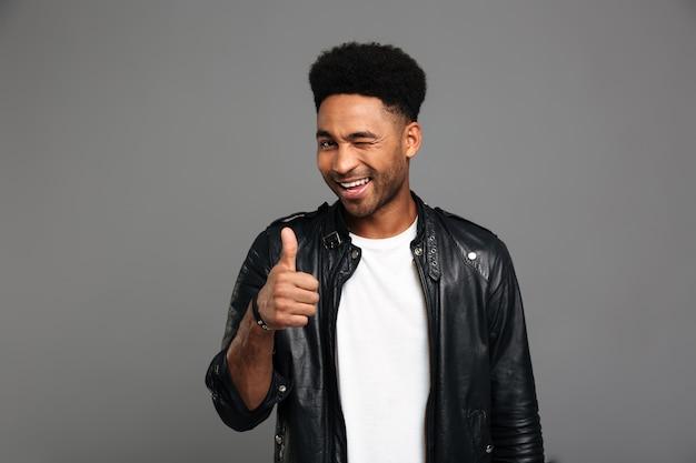 Joven atractivo muchacho afroamericano en chaqueta de cuero guiña un ojo mientras muestra el pulgar hacia arriba gesto