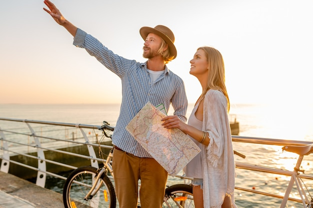 Joven atractivo y mujer viajando en bicicleta, sosteniendo mapa y turismo, pareja romántica en vacaciones de verano junto al mar al atardecer, amigos divirtiéndose juntos