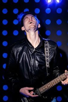 Joven atractivo músico de rock tocando la guitarra eléctrica y cantando estrella de rock en el fondo de spotli ...