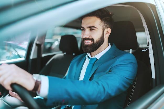 Joven atractivo próspero empresario caucásico en traje azul conduciendo su automóvil.