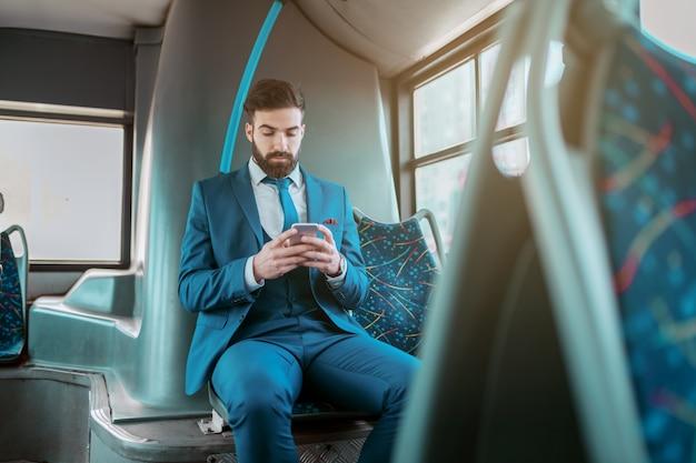 Joven atractivo serio empresario barbudo caucásico en traje azul sentado en un autobús público y utilizando teléfonos inteligentes.