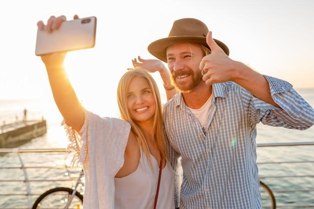 Joven atractivo sonriente feliz hombre y mujer viajando en bicicleta tomando fotos selfie en la cámara del teléfono, pareja romántica junto al mar en la puesta de sol, traje de estilo boho hipster, amigos divirtiéndose juntos