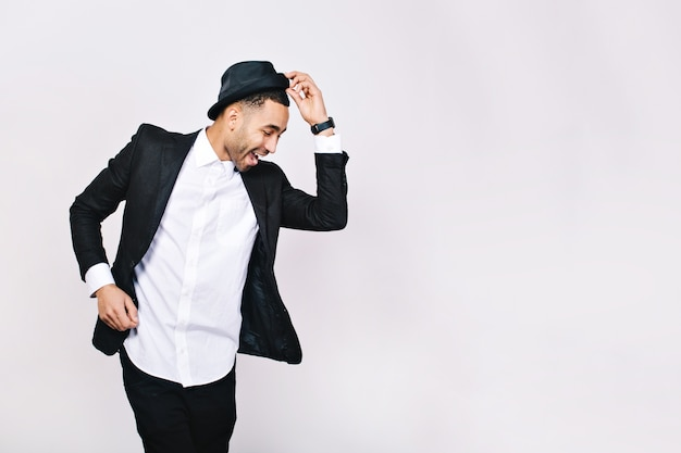 Joven atractivo en traje bailando, divirtiéndose. perspectiva elegante, sombrero, empresario exitoso, feliz, expresando verdaderas emociones positivas, gracioso.