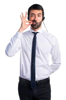 Joven con un auricular haciendo gesto de silencio