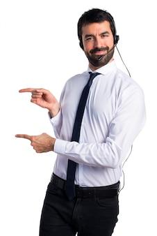 Joven con un auricular que apunta a la lateral Foto gratis