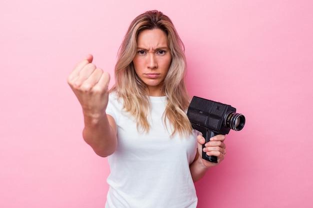 Joven australiana filmando con una cámara de video vintage aislada mostrando el puño a la cámara, expresión facial agresiva.
