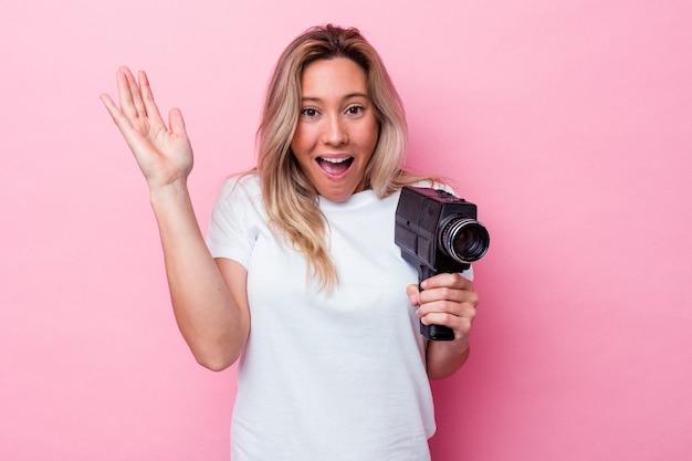 Joven australiana filmando con una cámara de video vintage aislada recibiendo una agradable sorpresa, emocionada y levantando las manos.